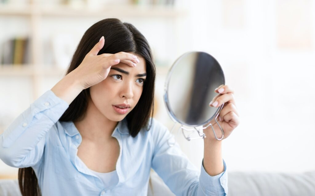 Problem Skin. Worry Asian Woman Looking In Round Mirror And Touching Forehead