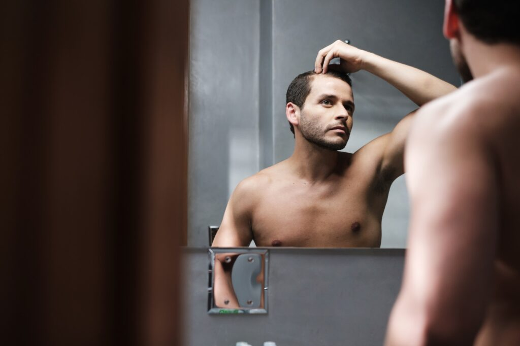 Young Man In Bathroom Worried About Premature Receding Hairline